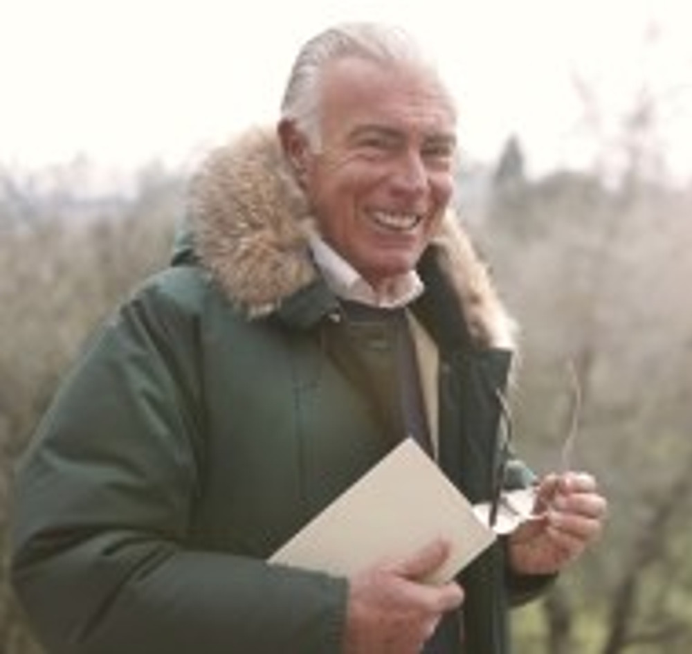 man in green parka jacket holding white book