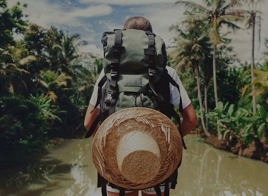 Traveler%20woman%20with%20backpack%20standing%20near%20big%20tropical%20river%20at%20sunny