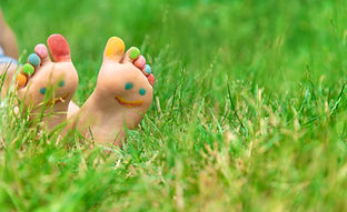 Children's feet with a pattern of paints smile on the green grass. Selective focus. nature