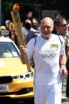 Patrick Stewart running with the Olympic torch in Croydon, ahead of the London 2012 Olympic Games.