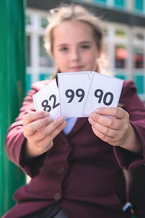 Image of pupil holding up Maths numbers.jpg