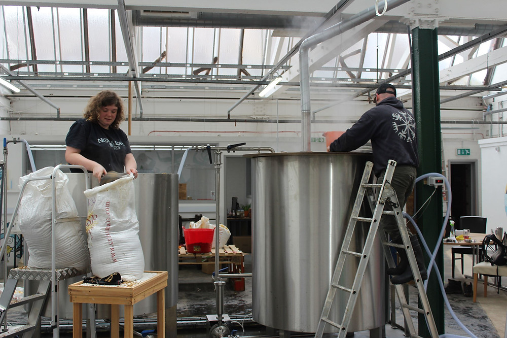 Katie Marriott digging out the mash tun & Ross Nicholson preparing the copper