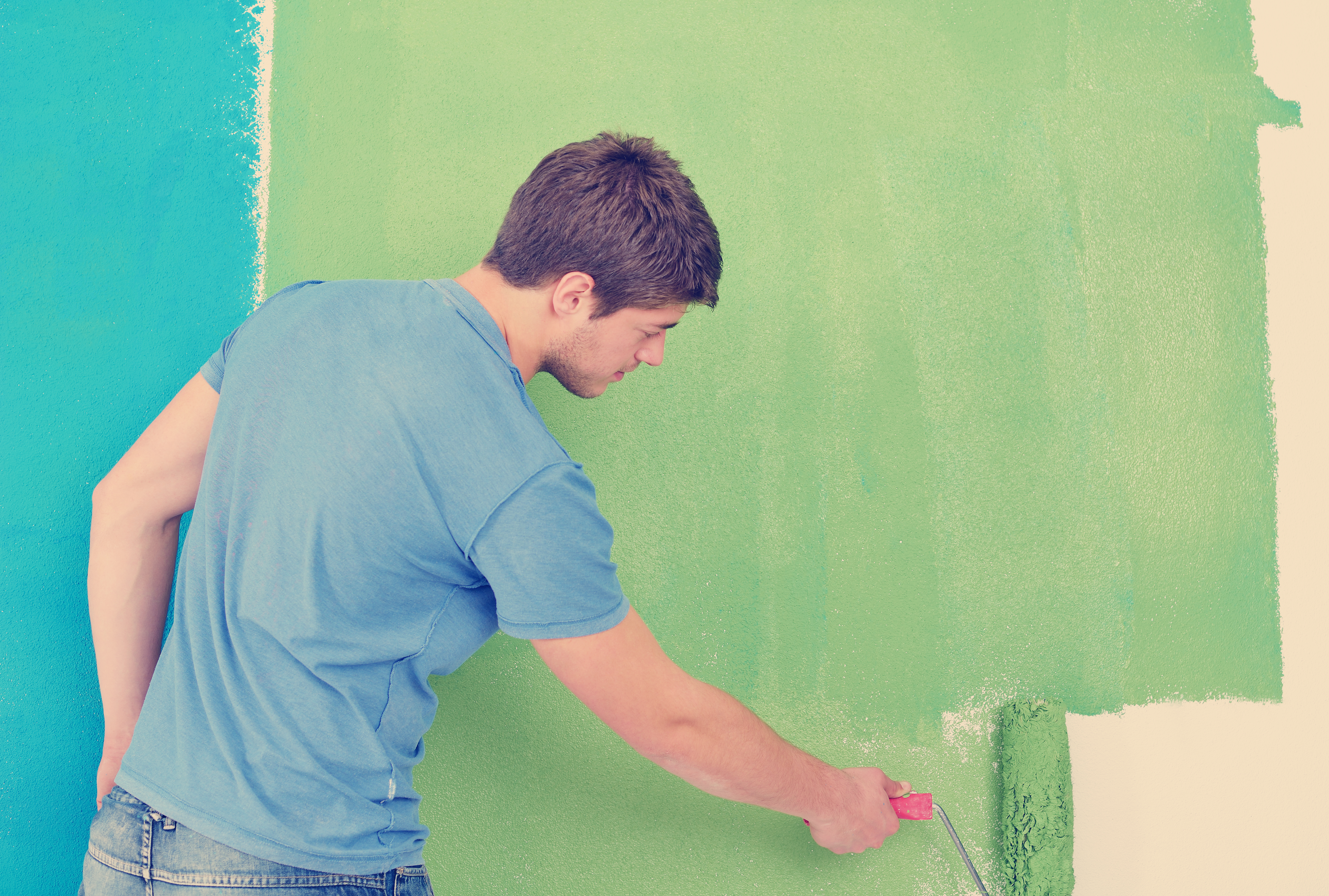 happy-couple-paint-wall-at-new-home-PXAD