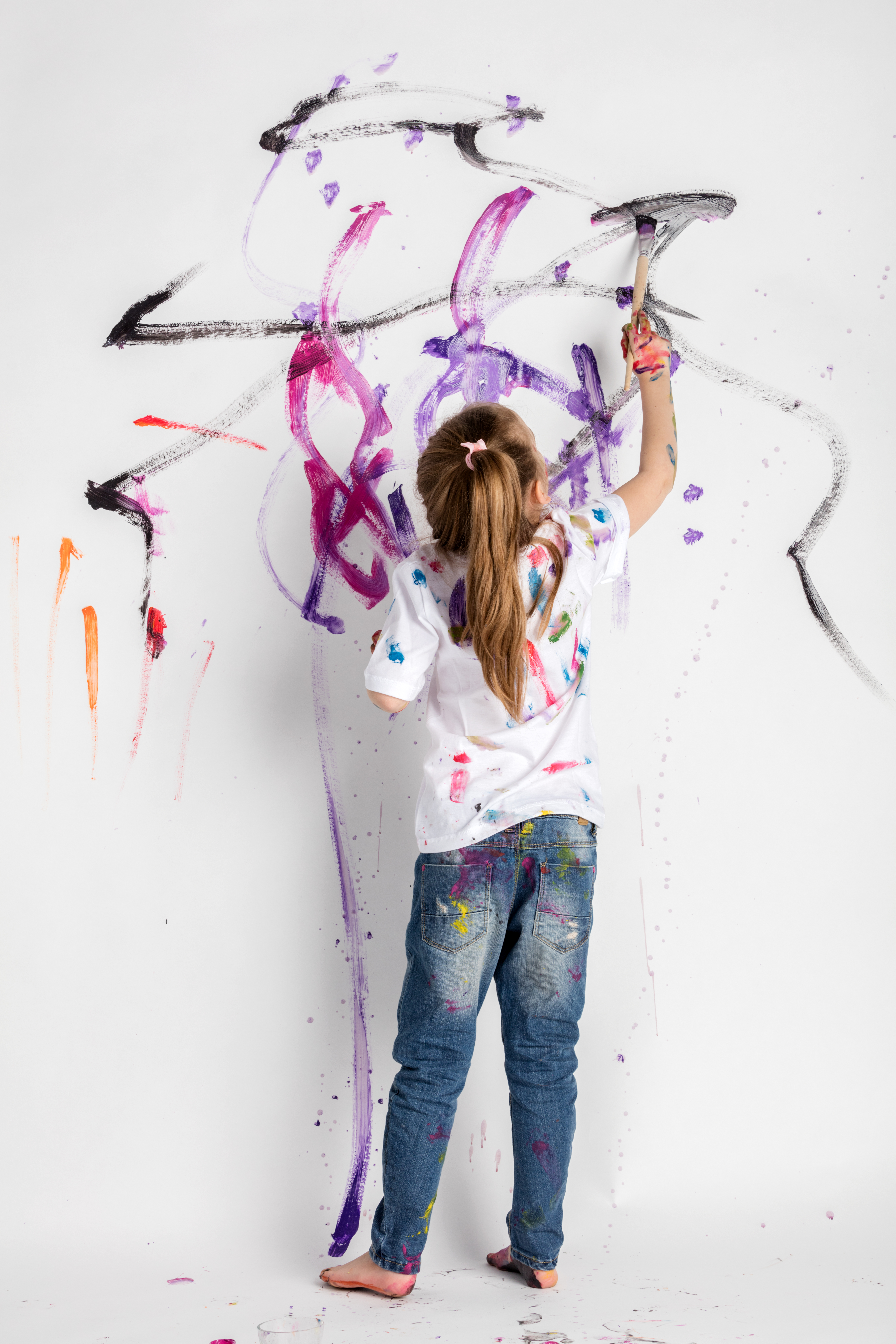 little-girl-decorating-a-white-wall-with