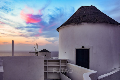 Colourful sunset by the windmills, Santorini, Greece