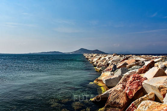 Fisherman on rock barrier of the Palatia, Naxos, Greece