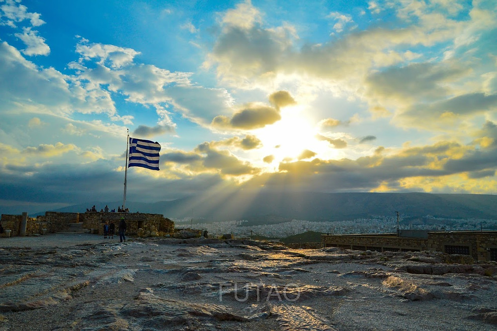 The Greek Flag swaying proudly atop Acropolis Hill, Athens, Greece