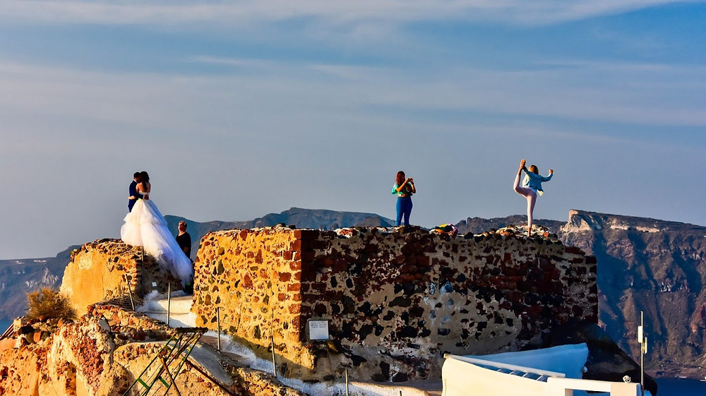 Bad tourists perched on the wall of an ancient castle in Santorini, Greece
