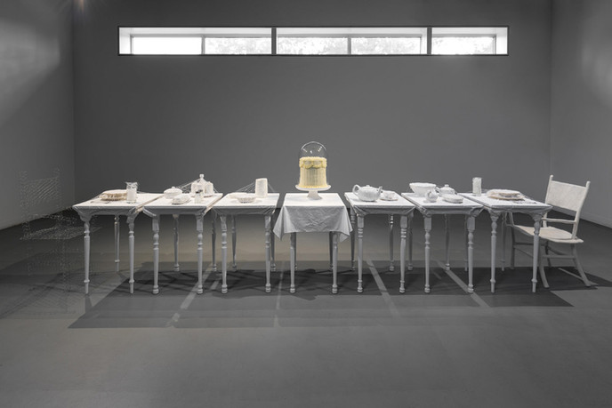 Between Me and Her, found tableware, vanilla cake with buttercream, glass cloche, thread, beads, wool roving, chicken wire, tablecloths, and wood, dimensions variable, 2021