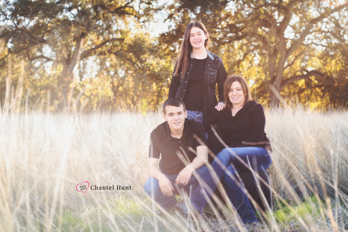 Family of three in grassy field