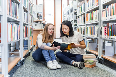 Two young girls sitting on the library floor reading books in the Rivers Reading program provided by River City Academy