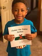 """Children with their copies of """"Clunker the Clumsy Caribou"""" book"""