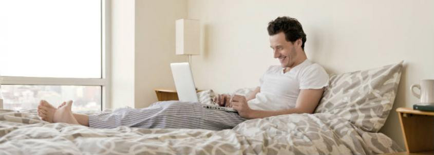 A man lies in bed in pyjamas, propped up on a pillow, using his laptop. His head is angled forward and his spine is curved.