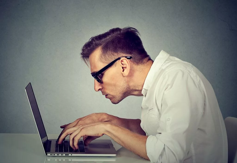 A man is typing on a laptop. His body is in an unnatural, comfortable and dangerous position: his elbows are too high, his spine is curved, his shoulders are hunched, his head is angled downwards and he has 'forward head posture', also known as 'chicken neck'