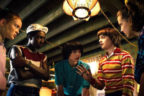 A still from the cult Netflix series, 'Stranger Things', in which the central group of young characters have gathered together to decide their plan of action
