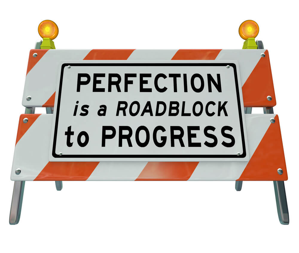 "Roadblock sign with ""PERFECTION is a ROADBLOCK to PROGRESS"" written on it"
