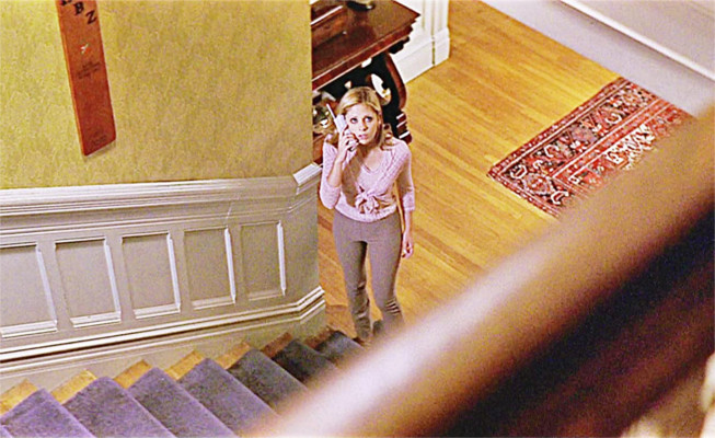 In the movie Scream 2, Cici (played by Sarah Michelle Gellar) is on the phone with the serial killer 'Ghost Face' who has told her he is in her house. She's at the bottom of her staircase after hearing a noise upstairs and is preparing to ascend the stairs to investigate.