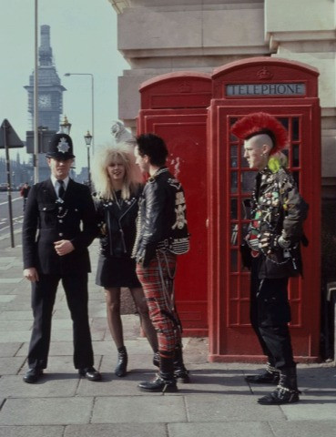 Three punk rockers and a policeman pose together smiling next to a red telephone box. In the background is Big Ben and the Elizabeth Tower