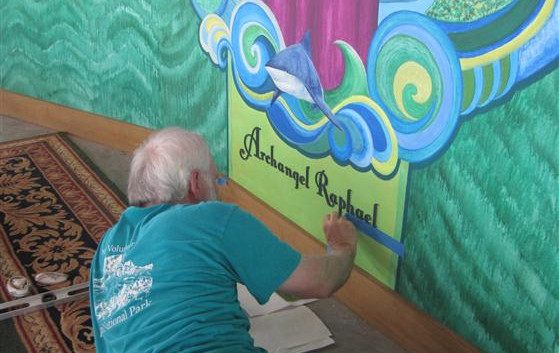 J. Bishop Affixing Scrollwork Letters to the Mural. … May 5, 2012