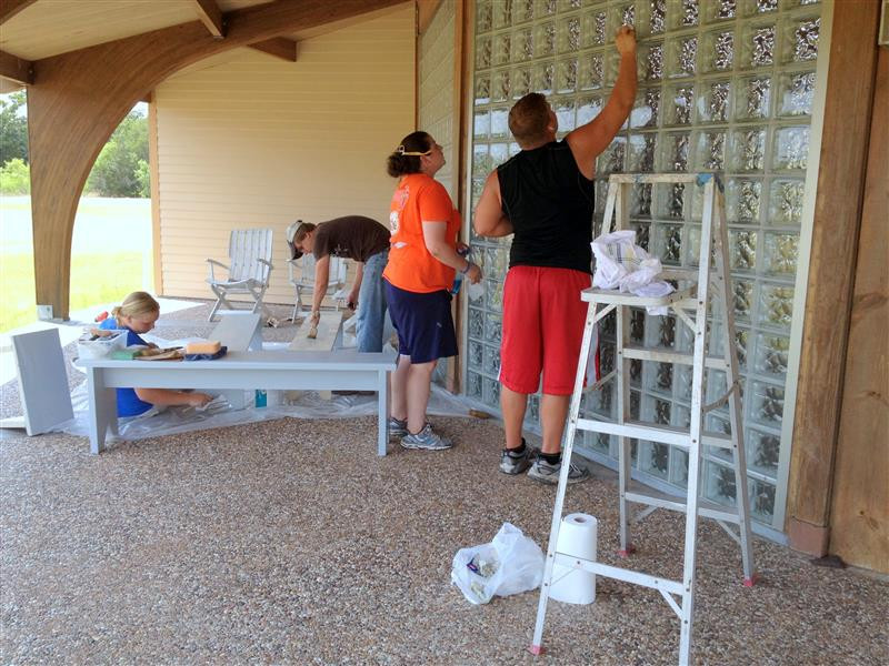 Thayne Tipton, Jacob Mason, Youth and Children's Minister Natalie Foreman, and Tristan Wendt painting benches and cleaning glass walls … July2, 2013