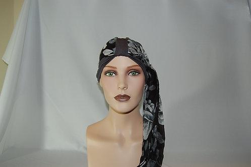 Turbante de gorrita hecha en tela de bambú color gris oscuro  con pañuelo  negro floriado fondo negro,