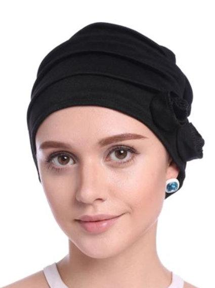 turbante de tela acrilica, con pliegues y  motivo de flor a un lado
