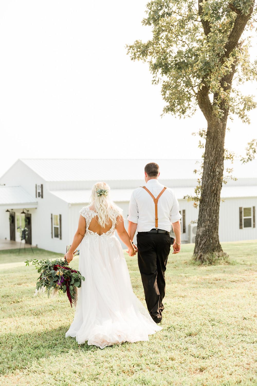 Bride and groom walking towards Southern Cedars wedding venue.