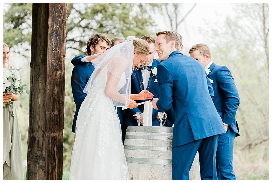 Bride and groom laughing while lighting unity candle.