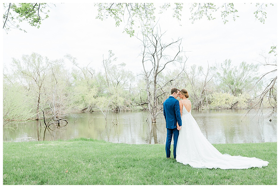 Bride and groom by a pond holding hands.