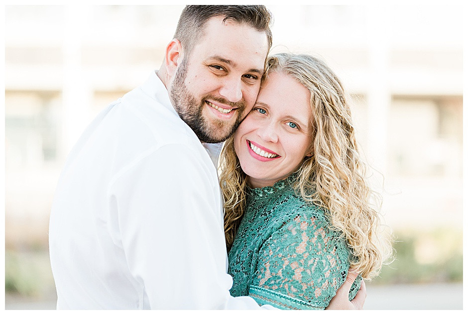 Couple hugging and smiling during their engagement session at Scissortail Park in Oklahoma City.