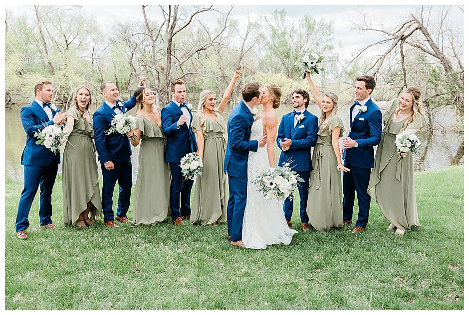 Bride and groom kissing with bridal party cheering.