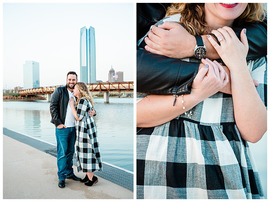 Couple embracing during their engagement session in Scissortail Park with water, the Devon tower, and downtown Oklahoma City in the background.