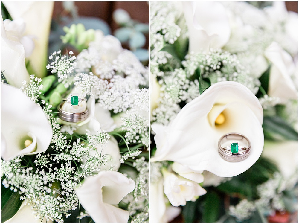 Emerald and diamond ring resting on a wedding bouquet.