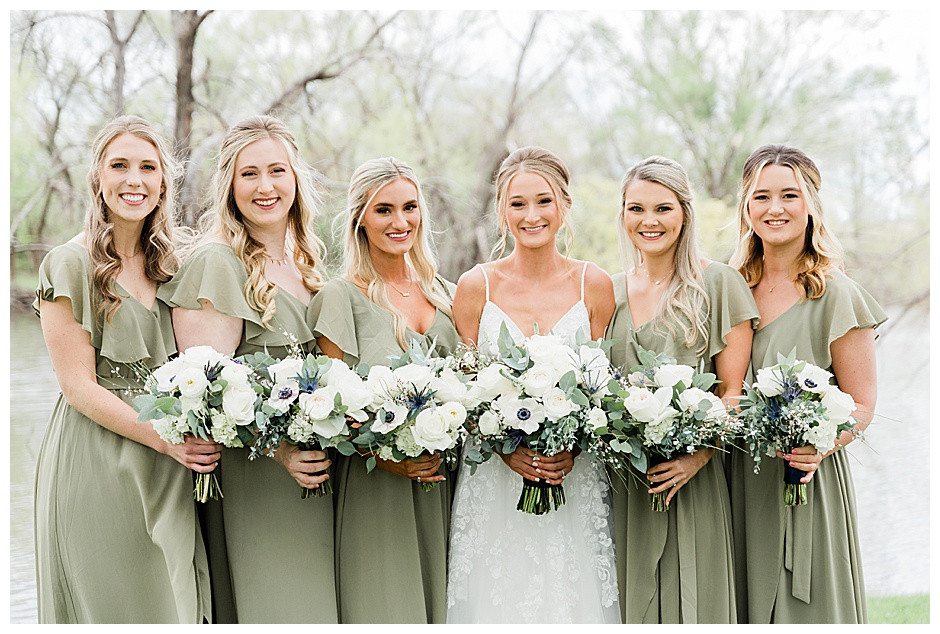 Bridal party smiling with bouquets.