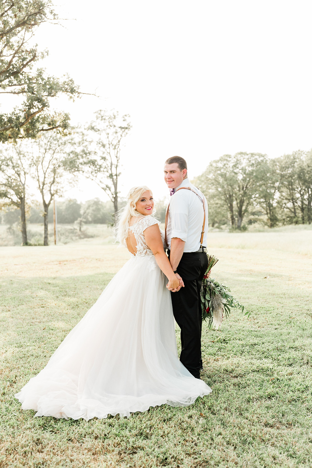 Bride and Groom standing in the field next to Southern Cedars wedding venue Oklahoma.