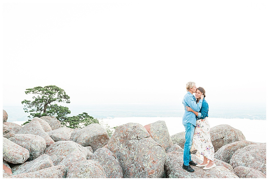 A couple standing on large rocks at Mt. Scott for their engagement session at sunrise.