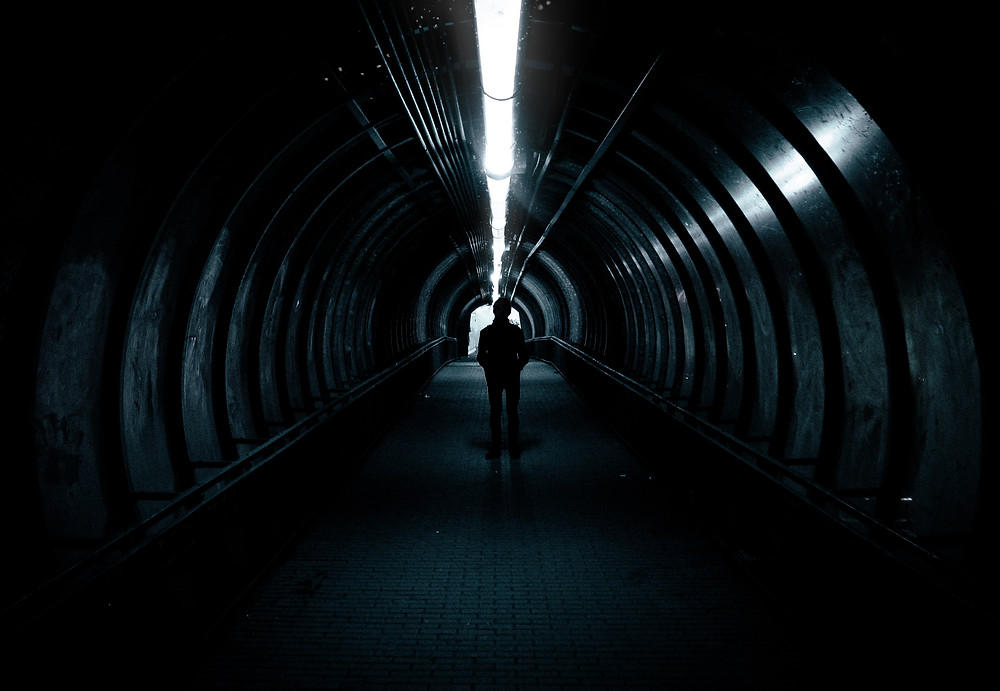 Man standing in dark tunnel.