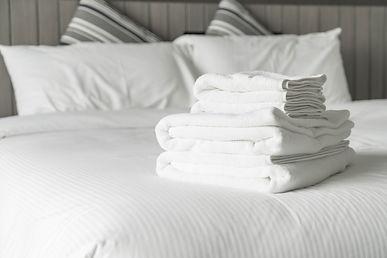 White bedding with white towel stack