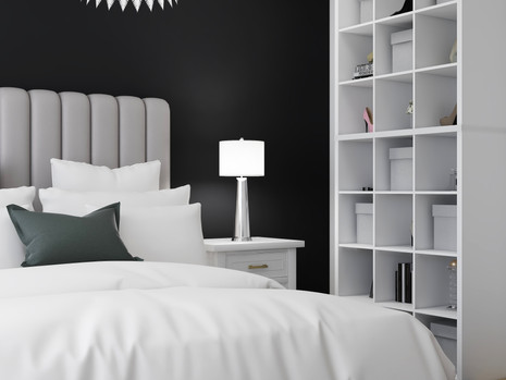 white end table beside a light grey bed