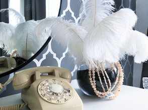 rotary phone beside black sand and ostrich feathers