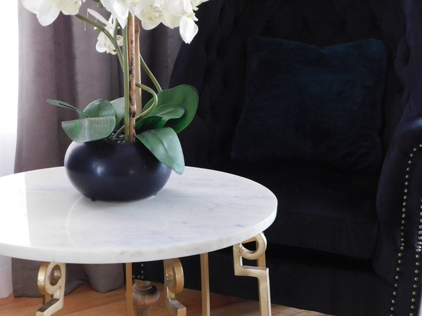 Giant Orchid on marble end table in the lounge of a big great room