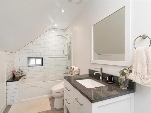 loft style farmhouse bathroom with subway tile and black grout
