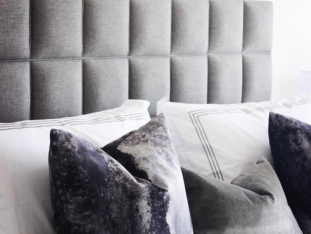 grey and navy throw pillows on tufted bed