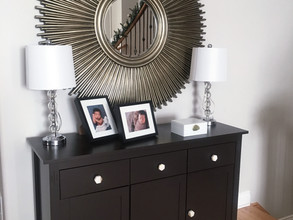 Storage console in mudroom with sunburt mirror, crystal lamps and geode decorative box