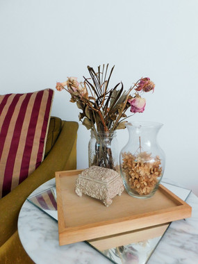 dried flowers in vase beside sofa