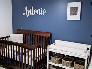 brown wood crib beside changing table wit baskets