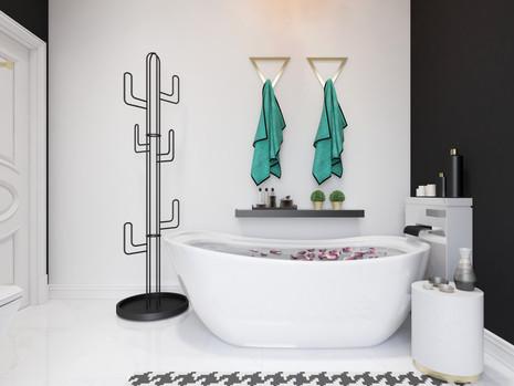 Cactus shaped coat rack beside a freestanding bathtub