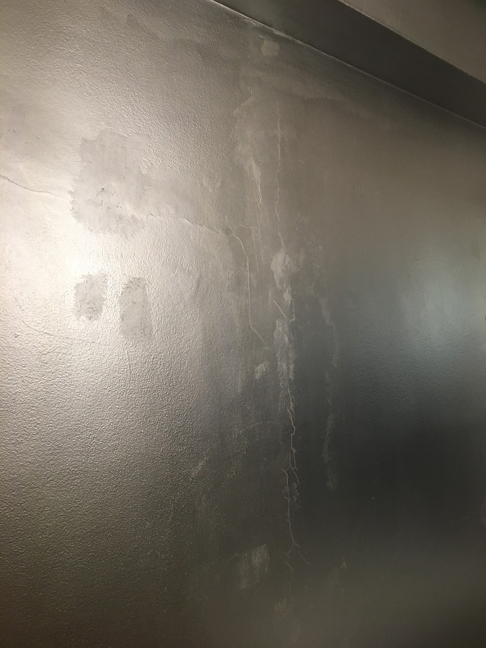 Painting over cracks on a wall with metallic paint