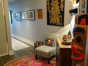 Red rug in condo entryway with artwork
