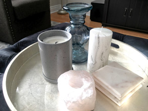 Ottoman tray with candles, coasters and other decor in modern and chic living room